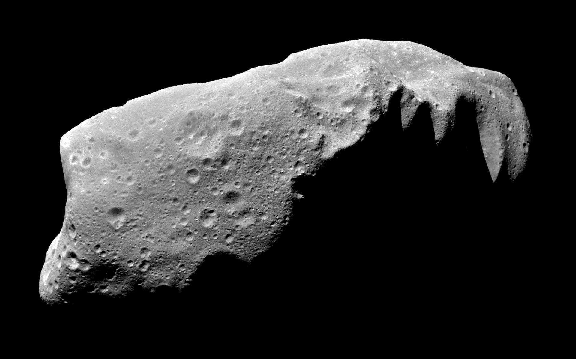 """Vypadal právě takto asteroid, který se před 66 miliony lety osudově střetl se Zemí? Je to možné, ačkoliv přesný původ tohoto """"temného a primitivního"""" poutníka Sluneční soustavou stále neznáme. Na složeném snímku planetka 243 Ida, navštívená v roce 19"""