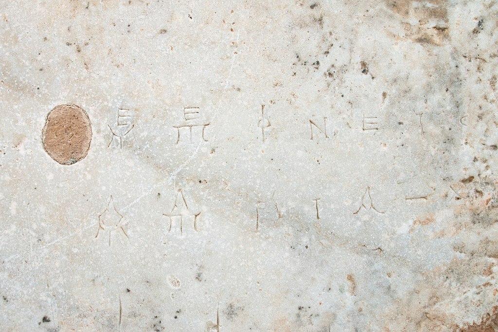 Mramorová deska s vyrytými hudebními nebo matematickými symboly, detail. Kredit: Wikimedia Commons.