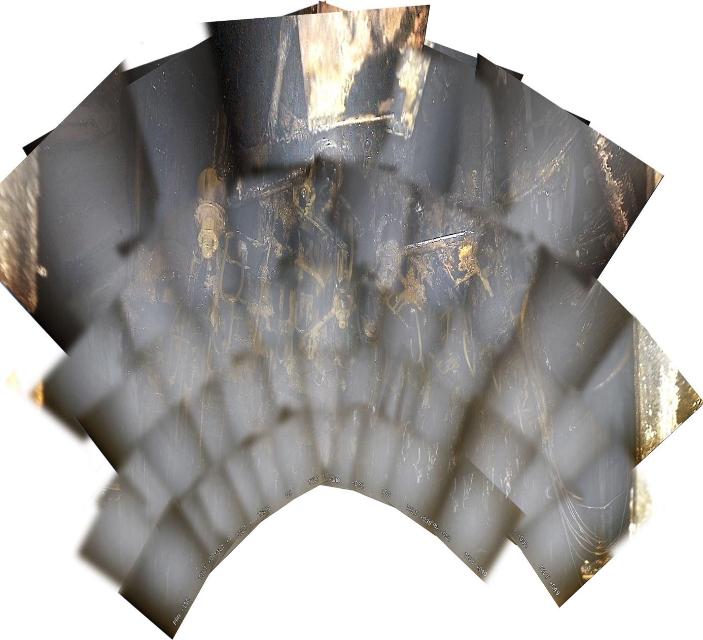 Pohled nahoru na spodní část tlakové nádoby reaktoru, opět seskládaný z mnoha fotografií. Je vidět jak poškozené, tak i nepoškozené části. (Zdroj TEPCO).