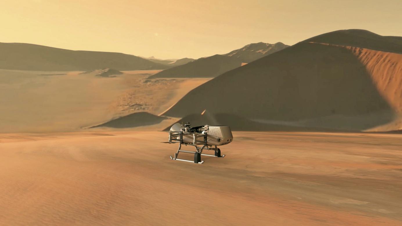 Umělecká předběžná představa o vzhledu dronu Dragonfly na Saturnově měsíci Titanu (zdroj NASA/JHU-APL).