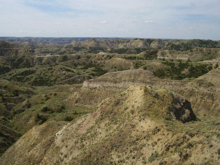 Pohled na pohřebiště dinosaurů z konce křídového období, sedimenty ze souvrství Hell Creek na území Hell Creek State Park ve východní Montaně. Kredit: V. Socha, červenec 2009. Využití snímku jen se svolením autora.