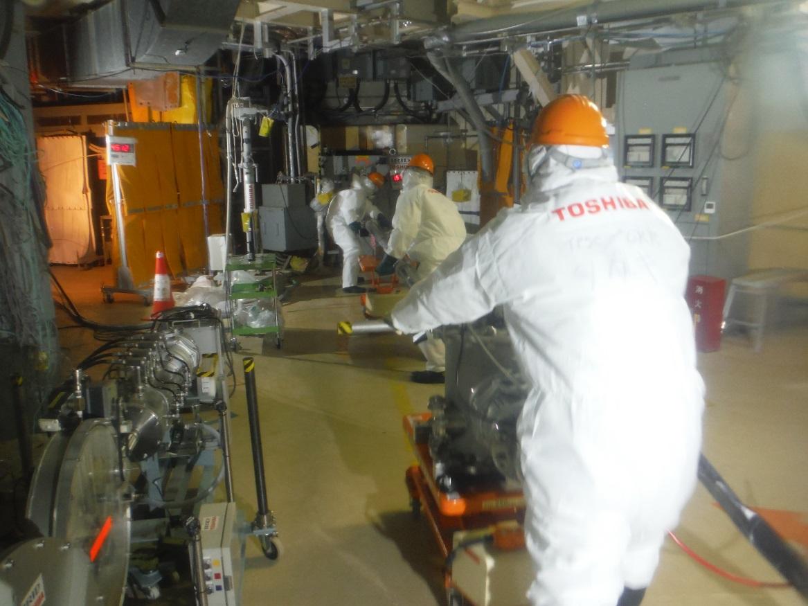 Pracovníci firmy Toshiba zavádí robota do potrubí (zdroj TEPCO).