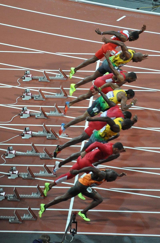 """Start finálového závodu v běhu na 100 metrů na Olympijských hrách v Londýně roku 2012. Nejrychlejší člověk historie, jamajský sprinter Usain Bolt, je zde v pořadí třetím sprinterem """"odzdola"""". Ani s dosaženou rychlostí 44,72 (a v letové fázi dokonce 4"""