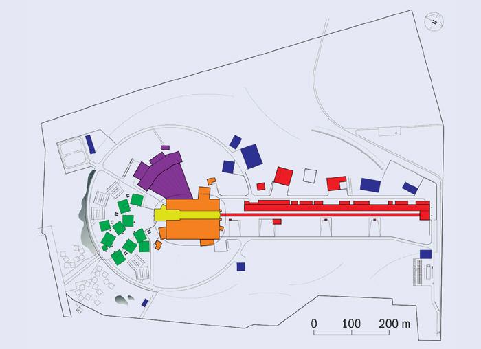 Schéma tříštivého zdroje neutronů ESS. Červeně jsou označeny budovy ukrývající urychlovač, žluté jsou místa ukrývající terč, oranžové a fialové stavby, ve kterých je experimentální zařízení, zelené jsou kanceláře a laboratoře, modré servisní budovy.