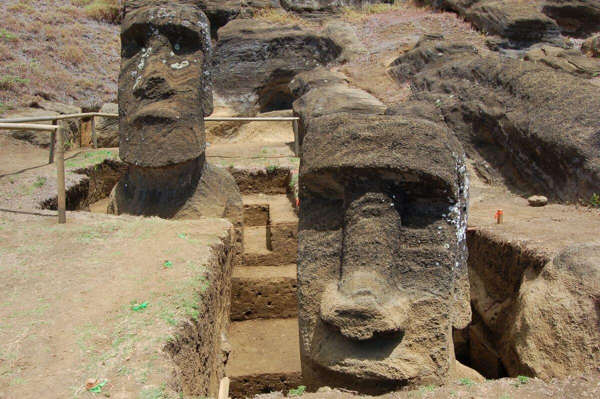 Během vykopávek prováděných týmem Jo Anne Van Tilburg v lomu Rano Raraku, Rapa Nui se objevil podstavec a vyšlo najevo, že zadní strany dvou soch jsou pokryty petroglyfy. Kredit: Easter Island Statue Project.