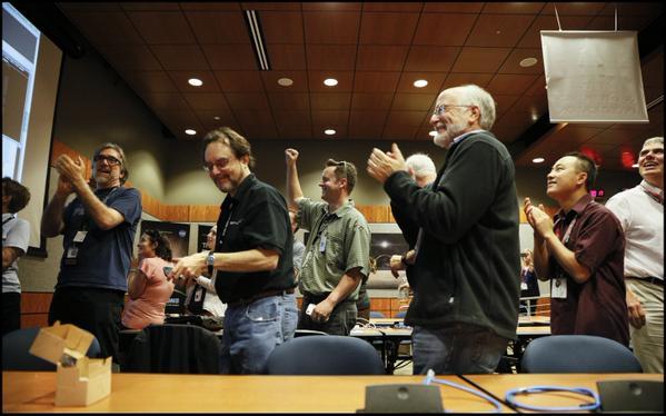 Malá úterní oslava (7.7.) členů týmu New Horizons. Chvilka zábavy a uvolnění mezi  pracovními povinnostmi. Letová kontrola potvrdila fázi blízkého průletu sedm dní před  největším přiblížením.  Kredit: NASA/NewHorizon