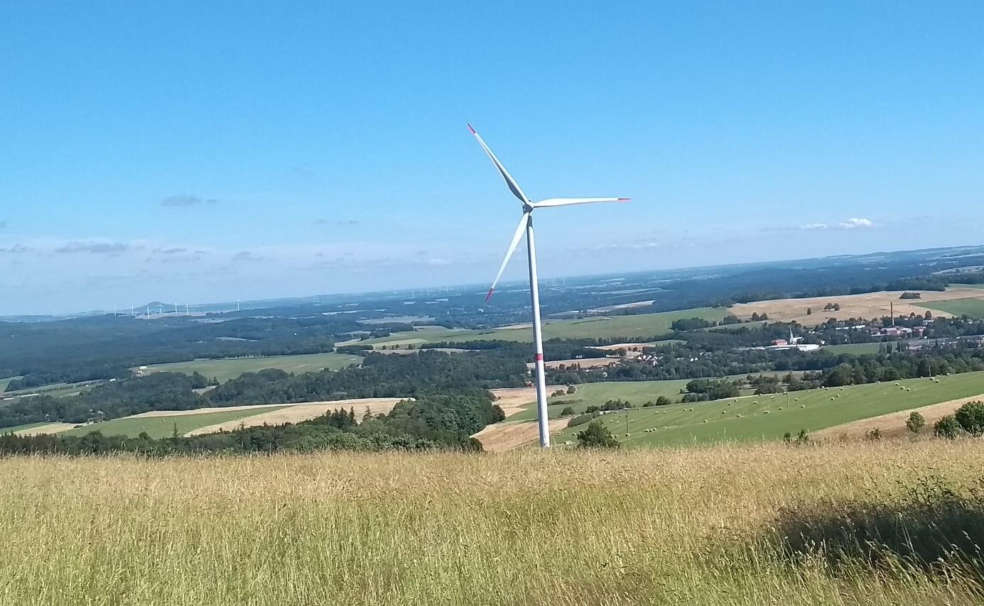 Decentralizované větrné turbíny a farmy by i u nás mohly přispět k přechodu k nízkoemisní elektroenergetice. V popředí osamělá turbína v Jizerských horách, v pozadí nalevo od ní pak skupina turbín v Polsku. (Foto Vladimír Wagner).