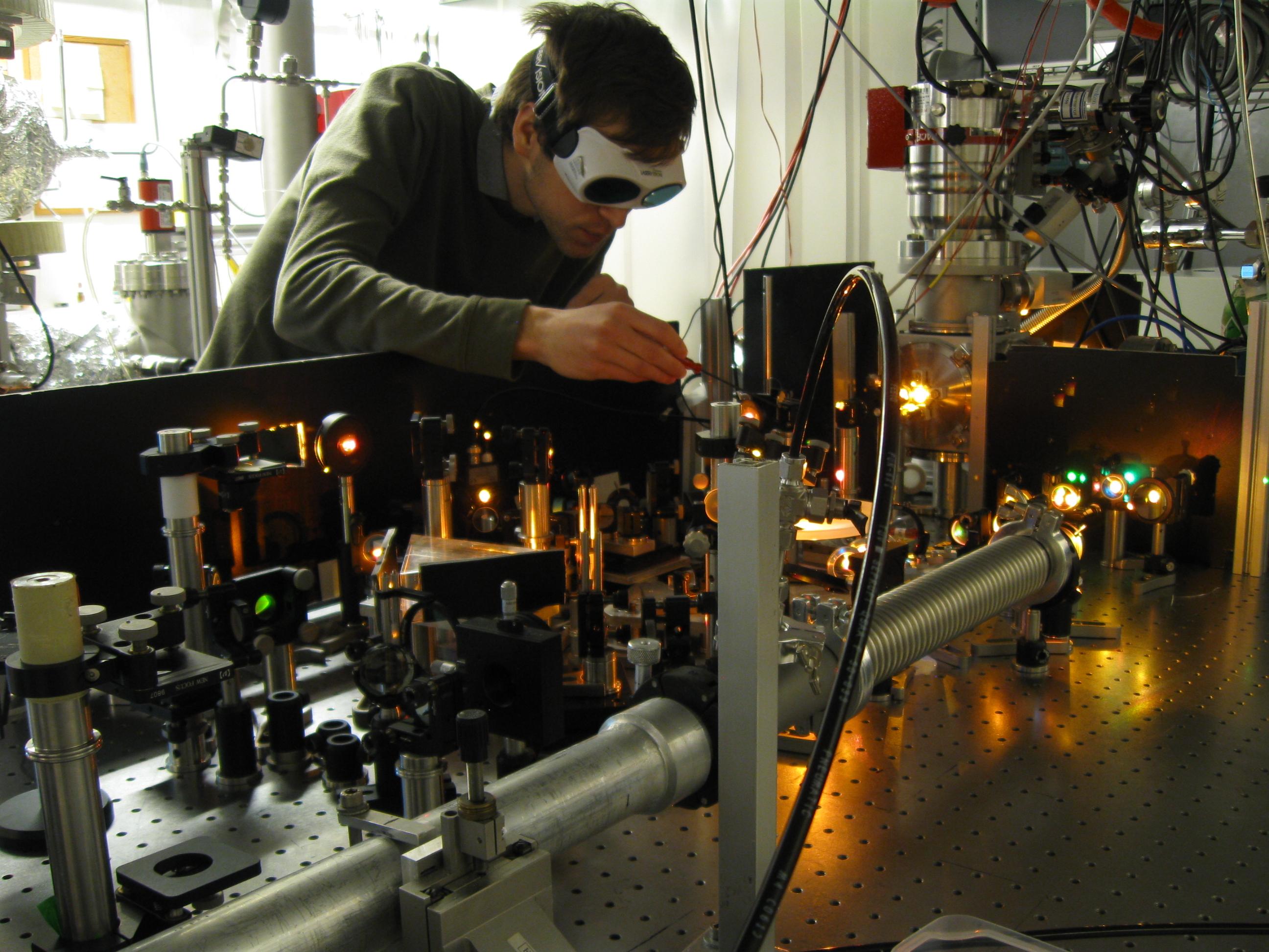 Práce na distribuci laserového svazku. Aby bylo dosaženo co nejkratších impulzů, musí být svazek spektrálně rozšířen pomocí vedení v tenké kapiláře – právě proto odlesky na zrcátkách hrají všemi barvami.