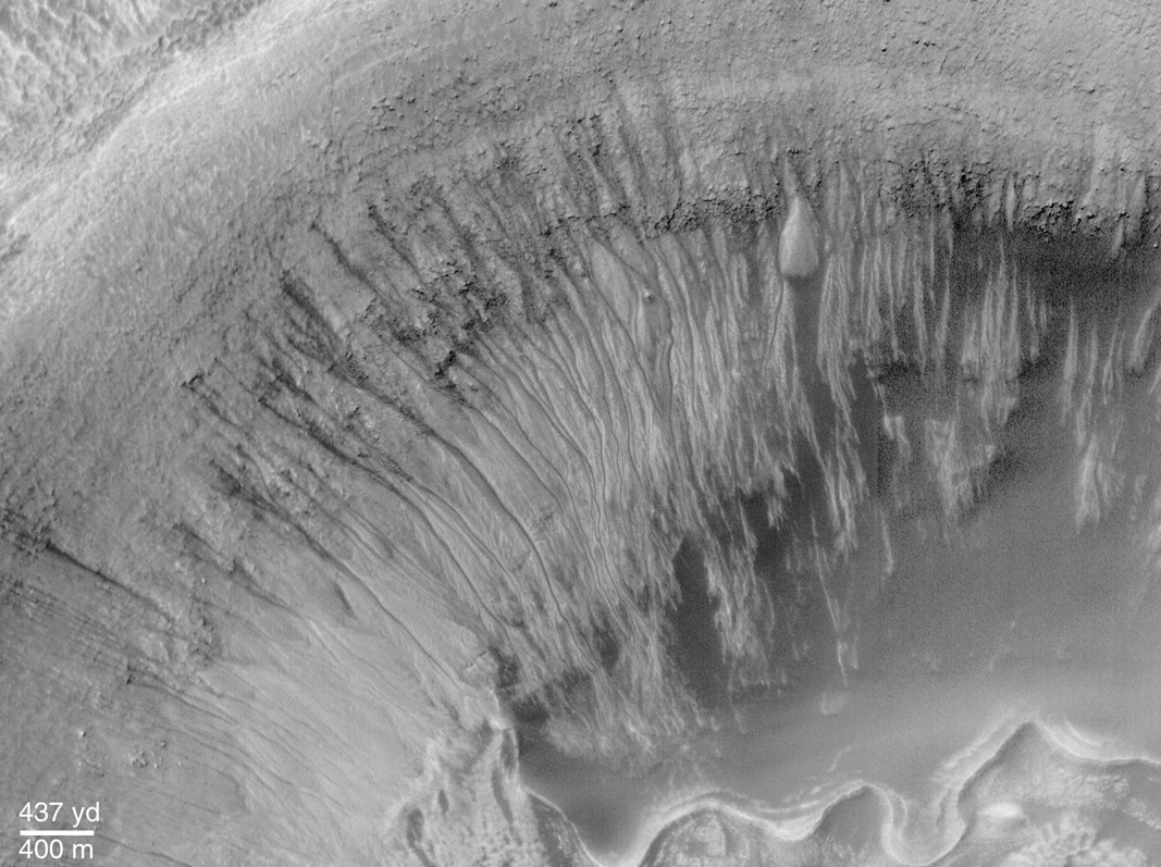 Snímek dne z června roku 2000 – fotka pořízená sondou Mars Global Surveyor. Jsou zde velmi dobře vidět koryta, která vytvořila tekoucí voda. Zdroj: http://apod.nasa.gov/