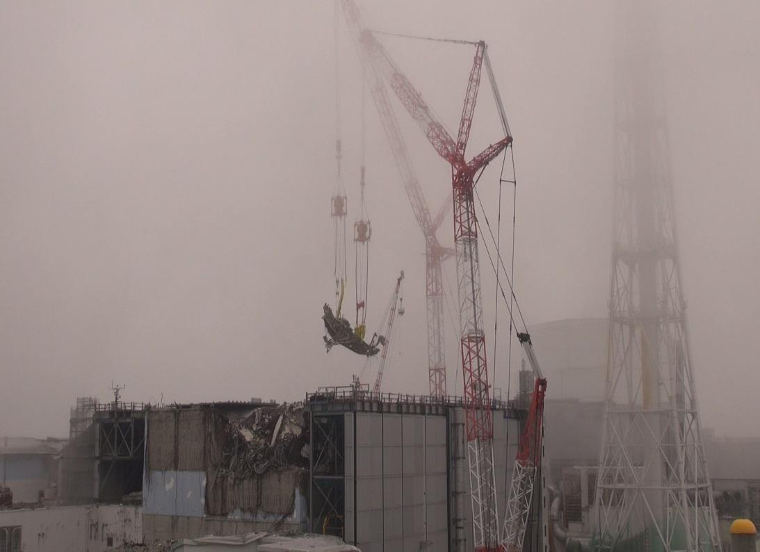 Vytažení zavážecího stroje pomocí dvojice na dálku řízených jeřábů (zdroj TEPCO).