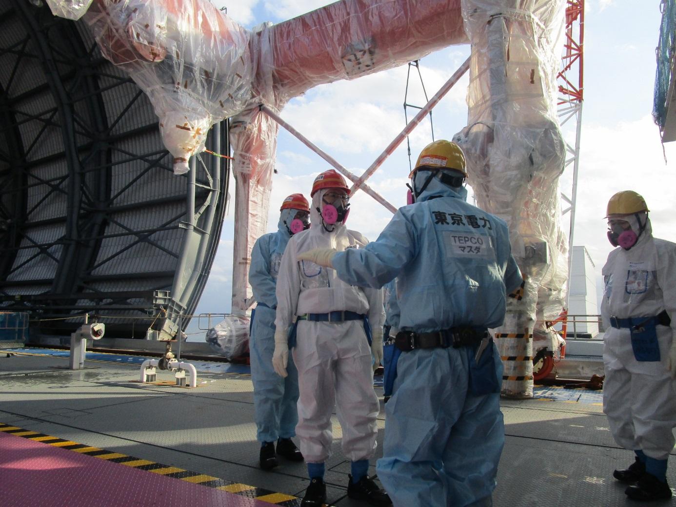 Guvernér prefektury Fukušima před novou horní části budovy třetího bloku a konstrukcemi pro jeřáby připravenými k instalaci (zdroj TEPCO).
