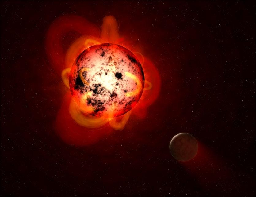 Hypotetická exoplaneta obíhající okolo velmi aktivního červeného trpaslíka v  představě umělce (zdroj NASA/ESA/G. Bacon (STSCI)).