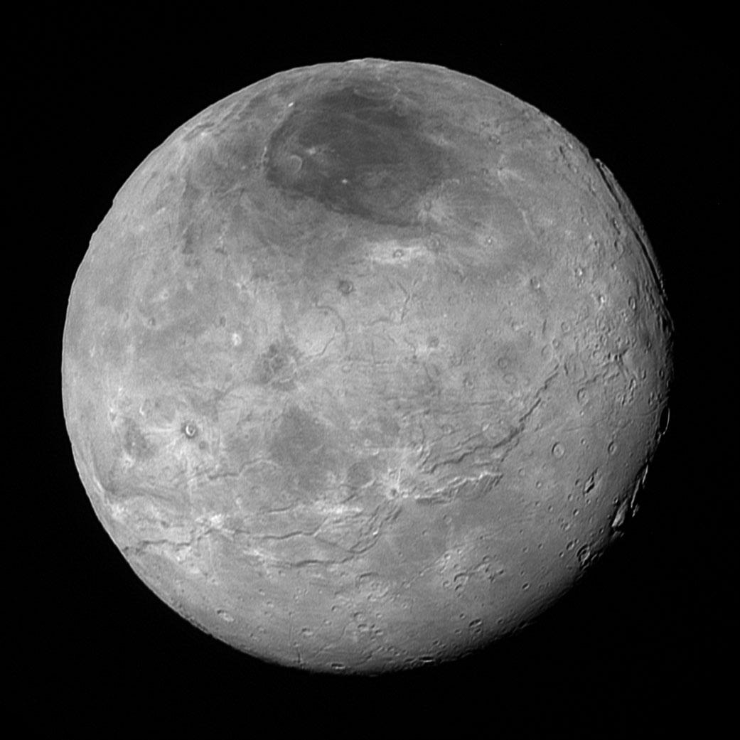 Snímek měsíce Charon pořízený zhruba 10 hodin před nejbližším průletem.kolem Pluta (vzdálenost 470 000 km). Jde o nekomprimovanou verzi snímku představeného jen pár hodin po průletu. Vidíme zde tektonické zlomy, relativně rovné p