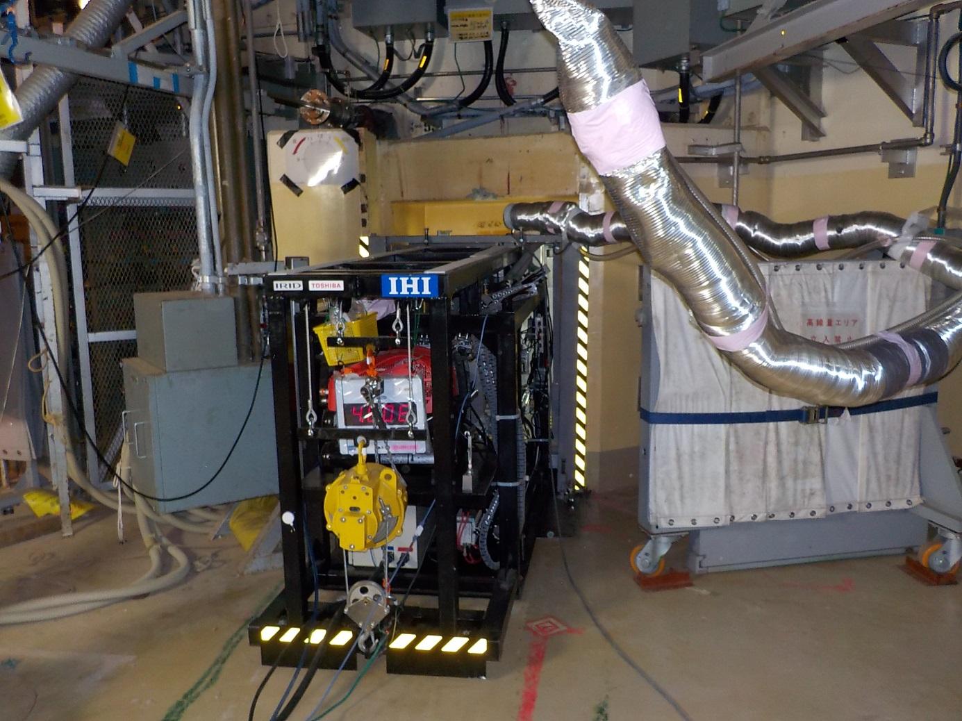 Příprava stroje na vrtání děr pro průchod robota do systému potrubí, která ho přivedou dovnitř kontejnmentu druhého bloku (zdroj TEPCO).