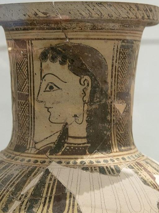 Dívka na hrdle keramické nádoby z ostrova Paru (Parosu). Náušnice je zakotvena také ve tváři, 700-500 před n. l. Archeologické muzeum na Mykonu. Kredit: Zde, Wikimedia Commons.
