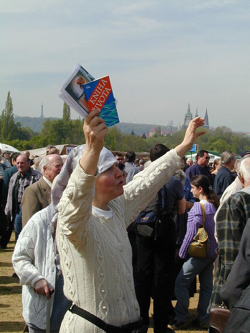 Žena sKnihou života a letákem s Aštarem Šeranem na Letné. Květen 2002. (Wikipedia)