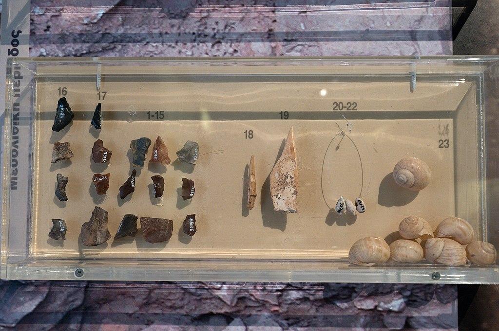 Hroty z mélského obsidiánu z jeskyně Franchthi jsou opět vlevo nahoře, a pod nimi pazourky. Mezolit, 7500 až 7000 let před n. l. Archeologické muzeum v Naupliu (Nafplionu). Kredit: Zde, Wikimedia Commons. Licence CC 4.0.