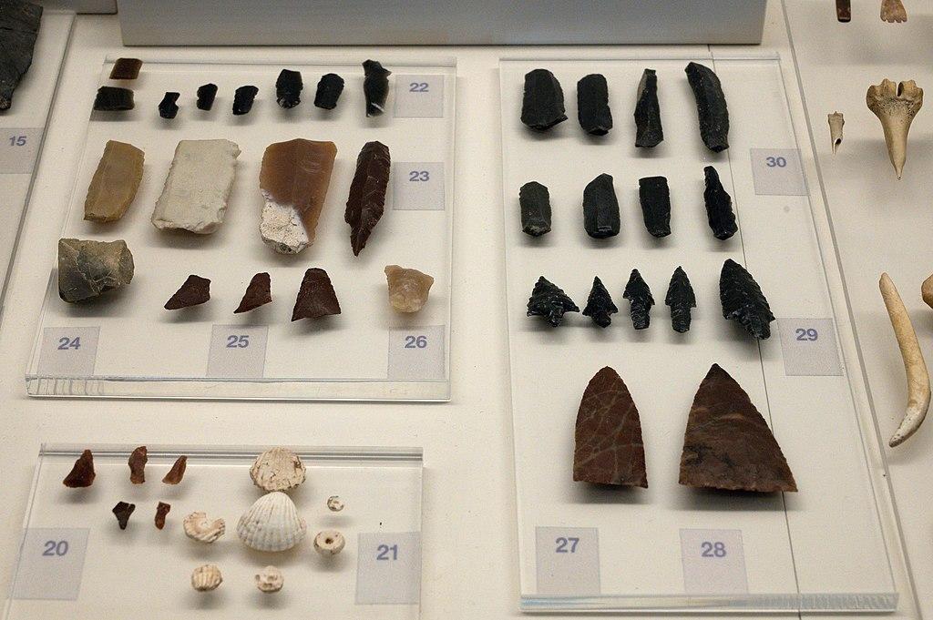 Neolitické nástroje z jeskyně Franchthi a rozpracované ozdoby z mušlí Cerastoderma glaucum. Obsidián (5800 až 3700 před n. l.) a pazourek (5800 až 5300 před n. l.). Archeologické muzeum v Naupliu. Kredit: Zde, Wikimedia Commons. Licence CC 4.0.