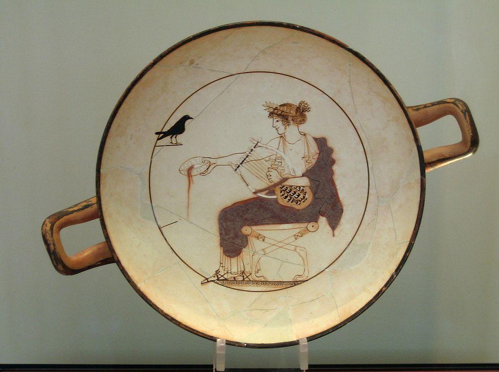 Apollón obětuje (alias krmí ptáka) než bude svou hrou vyjadřovat a ztvárňovat běh světa. Je k tomu ustrojen skoro po žensku, protože je nad protiklady, resp. je spojuje. Delfy, 460 před n. l. Archeologické muzeum v Delfách. Kredit: Tomisti, Wikimedia