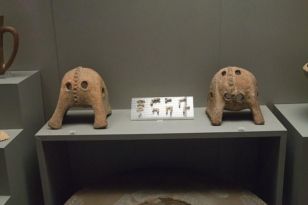 Keramické masky používané na Naxu při metalurgii olova a olověné úchytky používané k opravě rozbitých keramických váz, kolem 2500 před n. l. Národní archeologické muzeum v Athénách, inv. č. 6163 a 13311. Kredit: Zde, Wikimedia Commons.