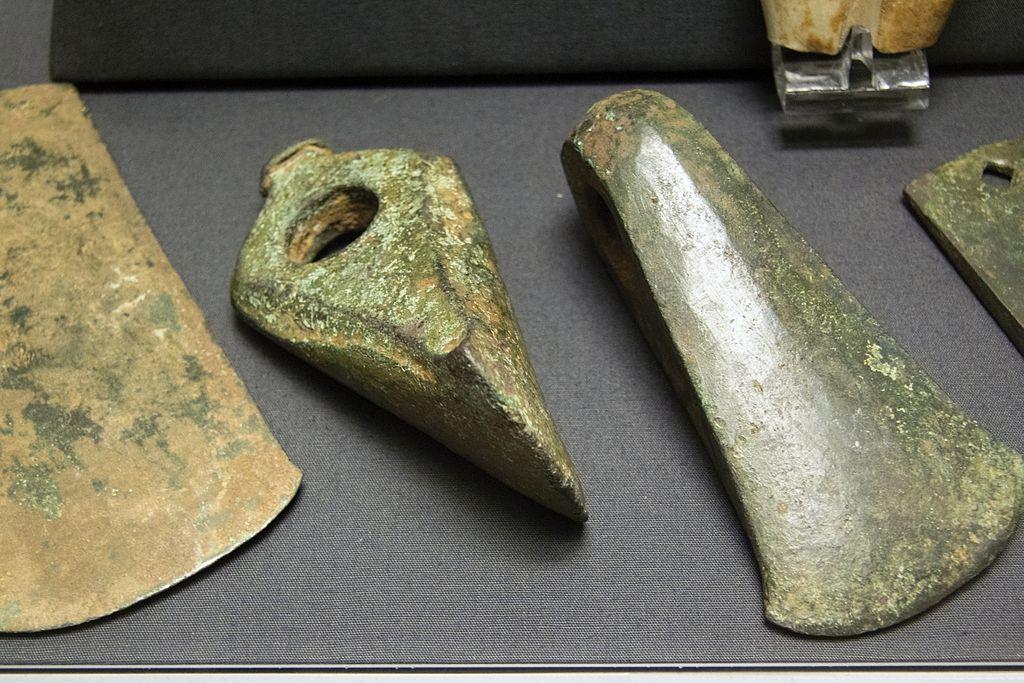 """Část depozitu nástrojů ze slitiny mědi tvrzené arzenem (""""arzenový bronz""""), pravděpodobně ke zpracování dřeva. Naxos, 2800–2200 př. n. l. Britské muzeum, GR 1969.12-31.1-8. Kredit: Zde, Wikimedia Commons."""