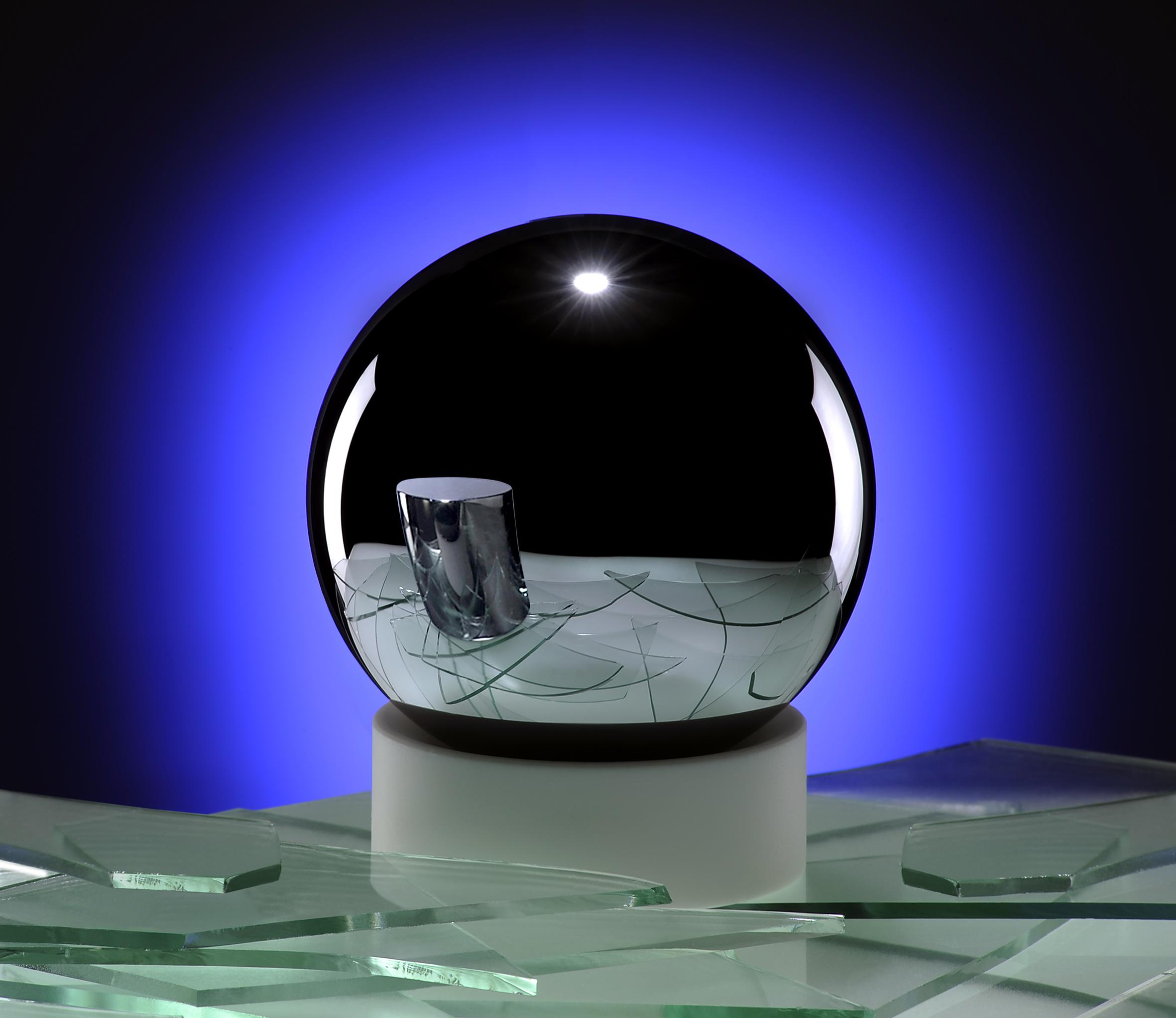Koule z velmi čistého křemíku Si28, nejkulatější objekt vyrobený člověkem, vyrobená v rámci projektu Avogadro. V odrazu lze vidět jednu z kopií mezinárodního prototypu kilogramu. Kredit: Physikalisch-Technische Bundesanstalt (PTB).