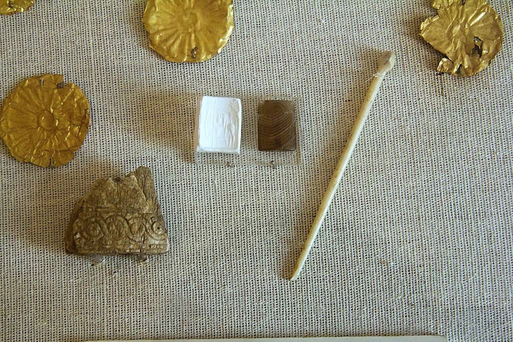 Část nálezů z mykénské vrstvy lokality Aplomata: Fragment reliéfu a jehlice ze slonoviny, zlaté plíšky a polodrahokamové razítko, 14. až 12. století před n. l. Archeologické muzeum na Naxu. Kredit: Zde, Wikimedia Commons. Licence CC 3.0.