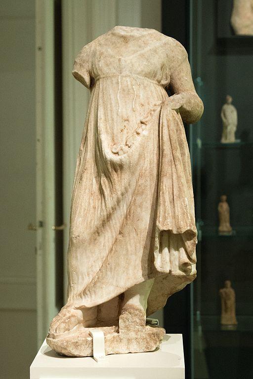 Torzo děvčátka oděného do chitónu, v jehož záhybu jsou astragaly (kůstky pro dětskou hru). Mramor, helénistická práce, 2. století před n. l. NG v Praze, NG P 578. Kredit: Zde, Wikimedia Commons.