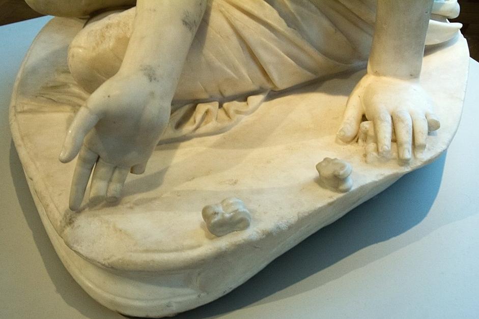 Malá dívka hraje astragalos (jednoduchá hra s kůstkami nebo kostkami), detail. Řím, 2. století n. l. podle helénistické předlohy. Altes Museum Berlin, Sk 494. Kredit: Zde, Wikimedia Commons.