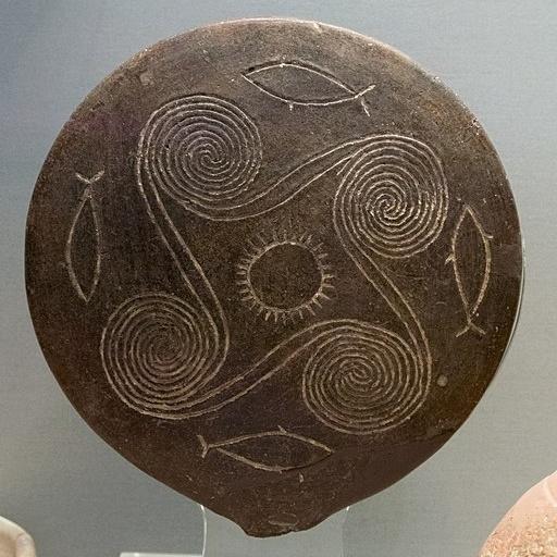 """Uprostřed je """"kolo Slunce"""", kolem něj čtyřnásobná spirála jako mořské symboly a 4 ryby. Raná kykladská doba bronzová, přechod I. a II. periody (EC I / II), Skupina (fáze) Kampos, asi 2800-2700 před n. l. Z hrobu 26 v Louros na Naxu. Národní archeolog"""