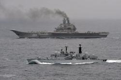 Dýmající Kuzněcov hlídám britským plavidlem. Kredit: Royal Navy.