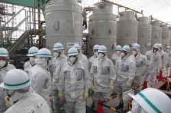 Pracovn�ci Mezin�rodn� atomov� agentury p�ed nov�m mobiln�m za��zen�m pro odstra�ov�n� radionuklid� z vody (zdroj TEPCO).