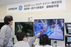 Dálkové ovládání při instalaci nosníku podpírajícího zhroucený zavážecí stroj u bazénu prvního bloku (zdroj TEPCO).