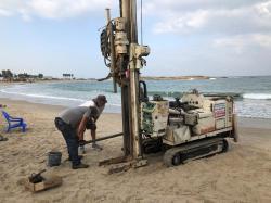 Vrtání vzorků sedimentů na izraelské pláži u Tel Doru. Kredit: T. E. Levy.