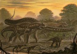 """Ekologická scéna z pozdní křídy Madagaskaru, kde dvojice dravých abelisauridů majungasaurů loví dospělého jedince sauropoda rapetosaura. Rapetosaurus krausei byl současníkem a zřejmě i jedním z nejbližších vývojových příbuzných evropského magyarosaura. I při délce """"pouhých"""" 15 metrů jej však velikostně značně překonával. Kredit: ABelov2014; Wikipedie (CC BY-SA 3.0)"""
