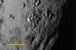 Snímek Pluta z kamery LORRI pořízený zhruba 90 minut před maximálním přiblížením. Hory jsou zřejmě tvořeny ledem. Zdroj: http://www.nasa.gov/