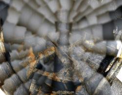 Pohled na prostor v centrální části seskládaný z mnoha fotografií ukazuje v dolní části silně poškozenou i úplně chybějící roštovou podlahu. Zároveň jsou vidět i popadané části. (Zdroj TEPCO).