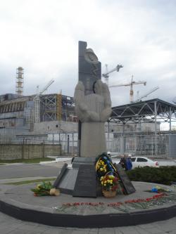 Památník obětem katastrofy a vzadu starý sarkofág.