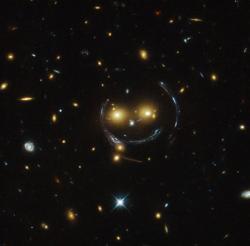 Pozorování gravitační čočky pomocí Hubblova dalekohledu, v centru obrázku je galaktická kupa SDSS J1038+4849 (zdroj NASA).