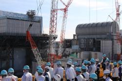 Inspekce týmu z Mezinárodní agentury pro atomovou energii, záběr na třetí blok připravený pro vyklízení palivových souborů a druhý blok s kontejnerem, který se využíván k průzkumu patra s bazénem s palivovými soubory (zdroj TEPCO).
