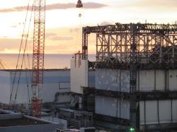 Jeřáb přemisťuje poslední panel provizorního krytu prvního bloku (zdroj TEPCO).