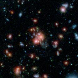 Obří galaktický klastr SpARCS1049+56 na kombinovaném snímku ve viditelném světle (Hubbleův teleskop) a v infračerveném oboru (Spitzerův teleskop).  Kredit: NASA/STScI/ESA/JPL-Caltech/McGill