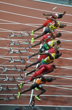 """Start finálového závodu v běhu na 100 metrů na Olympijských hrách v Londýně roku 2012. Nejrychlejší člověk historie, jamajský sprinter Usain Bolt, je zde v pořadí třetím sprinterem """"odzdola"""". Ani s dosaženou rychlostí 44,72 (a v letové fázi dokonce 47,56) km/h by neměl šanci proti některým druhům ptáků, šelem a kopytníků. Kredit: Darren Wilkinson; Wikipedia (CC BY-SA 2.0)"""