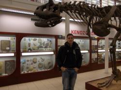 Autor u repliky kostry druhu Carnotaurus sastrei, vystavené od roku 2008 v expozici Chlupáčova muzea historie Země při Ústavu geologie a paleontologie PřF UK. Kostra osm metrů dlouhého teropoda je zblízka impozantní, i když se samozřejmě nemůže rovnat majestátnosti koster větších druhů, jako je severoamerický tyranosaurid Tyrannosaurus rex nebo jihoamerický karcharodontosaurid Giganotosaurus carolinii. Kredit: Vlastní snímek autora (pořízen Jakubem Sakalou v roce 2015).