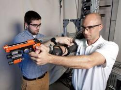 Dan Baechle (vlevo) z  výzkumného týmu, U.S. Army Research Laboratory Multifunctional Materials, vytvořil se svými kolegy prototyp zařízení snímající a eliminující třes paže. Zařízení má sloužit pro výcvik sniperů. Kredit: Doug Lafon