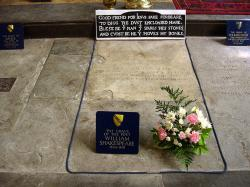 """Shakespearův hrob v kostele města Stratfordu nad Avonou. Epitaf v kameni vyhrožuje zlým osudem každému, kdo místo a ostatky nějak naruší: """"Dobrý příteli pro Ježíše, nechte ho,vykopat prach zde přiložený.Požehnaný muž, který tyto kameny šetří,a prokletý, kdo hýbe mými kostmi"""". U příležitosti 400. výročí  dramatikova úmrtí  byl prozkoumán aniž by kletbou opředený hrob musel být narušen.  Podle archeologů je v místě, kde by se měla nacházet jeho hlava, podivné prázdno.  Lebka se v hrobě nejspíš  nenachází.  Kredit: David Jones, CC BY 2.0, Wikimedia Commons"""