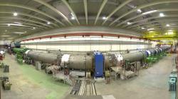 Samotný experiment NA62 je 270 m dlouhý. Jeho součástí je 120 m dlouhá vakuová komor, která je na fotografii. V jejím nitru je celá řada detektorů částic. Zakřivení na fotografii je dáno perspektivou fotografování. (Zdroj CERN).