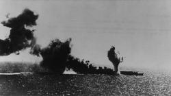 Ikonický snímek zbitvy vKorálovém moři – hořící lehká letadlová loď Šóhó. Kredit: Public Domain / Wikimedia Commons.