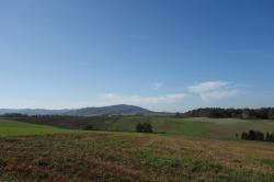 Pohled zvrchu Janský sloup (316 m n. m) ve směru na jihozápad. Jeden bludný balvan na Hoheneggerově mapě se nacházel napravo ve vzdálenosti cca 850 m, druhý cca 850 m nalevo. Vpozadí Libhošťská hůrka (494 m n. m.) – 1,5 km dlouhý hřeben pokrytý lesem, k