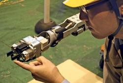 Pracovník firmy Toshiba předvádí robota, právě ukazuje kleště, které se později poprvé dotkly zbytků aktivní zóny (zdroj Fukusima-news.ru).